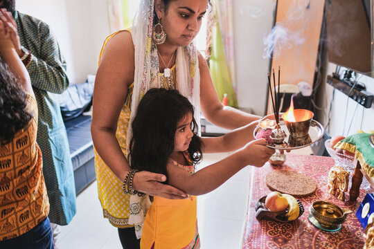 Indian family celebrate hindu event together at home - Traditional dress and religious celebration - Parents and children love