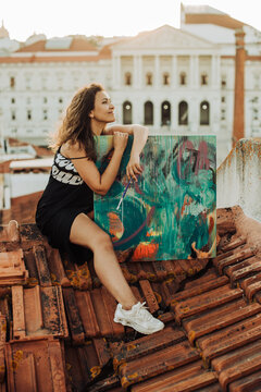Female painter sitting on tiled roof with her artwork