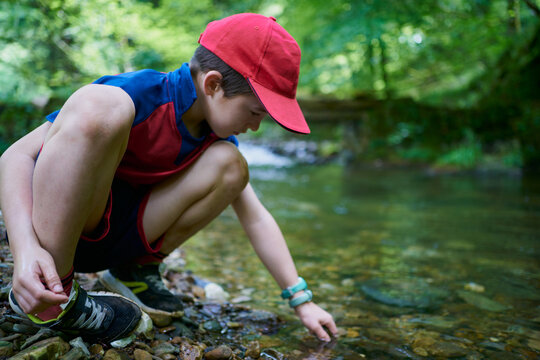 child with red hat by the river bank playing with water and stones in the forest