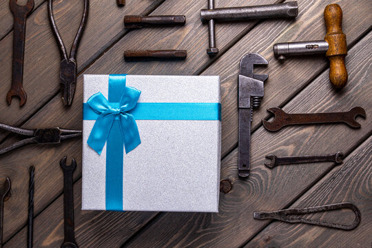 A gift on the background of Fathers ' Day, a postcard on a rustic background with repair tools and a gift box