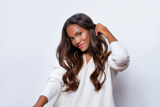 Happy Black Girl Smile in White Wool Sweater with long curly hair. Portrait of beautiful black woman posing against a light wall touching her long curly hair with her hand