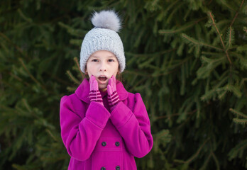 Portrait of surprised girl in pink coat and knitted hat on green trees background
