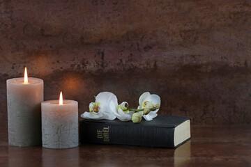 Bibel mit Kerzen und Orchidee