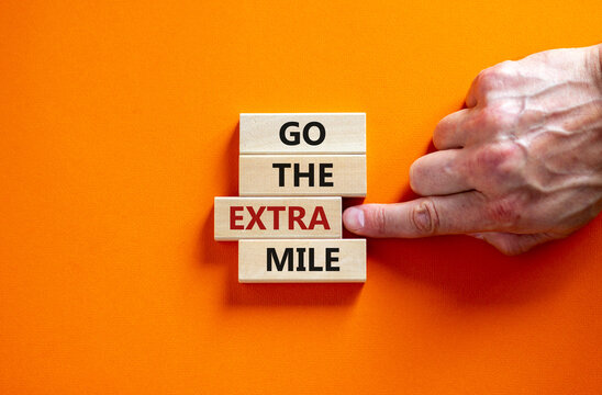 Go the extra mile symbol. Wooden blocks with words 'Go the extra mile'. Male hand. Beautiful orange background. Business and go the extra mile concept. Copy space.