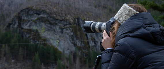 A female photographer captures photo with DSLR camera of beautiful landscape scenery in nature