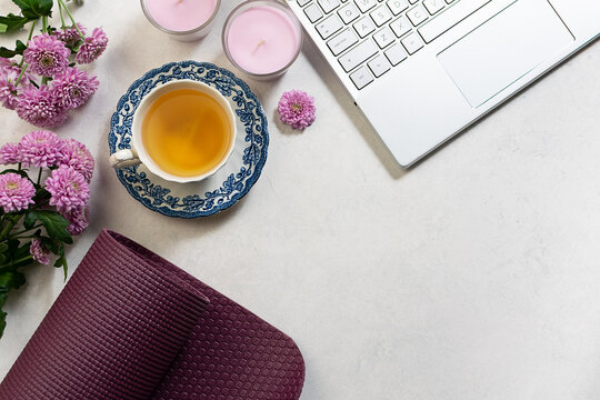 Online yoga training banner with laptop, yoga mat, aromatic candles and herbal tea on white marble table top view.