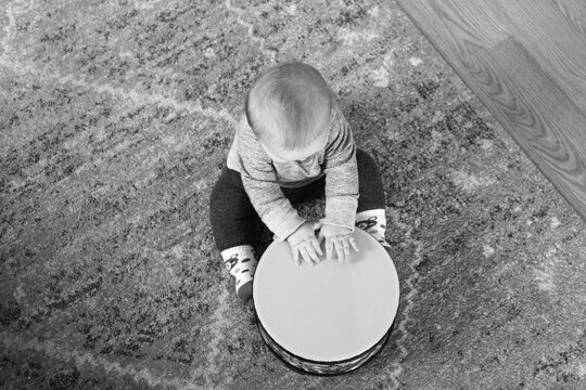 6 month old baby playing drum while seated on a rug on the floor; black and white image from bird's eye view