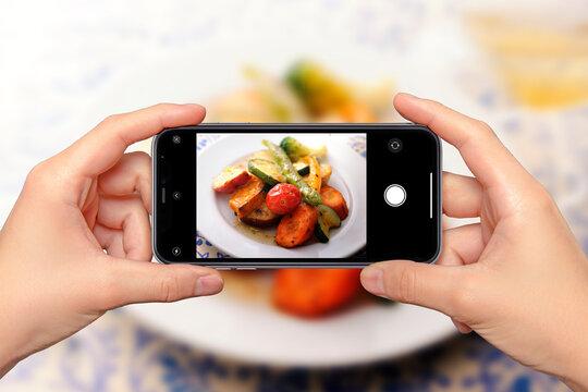 レストランで料理をスマートフォンで撮影しているイメージビジュアル