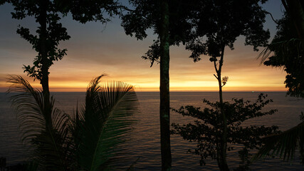 The sunset with views of the sea and palm trees. The sun goes below the horizon. An orange ray of...