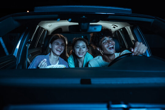 Portrait of three young friends looking emotional, laughing while sitting together in the car and watching a movie in a drive in cinema