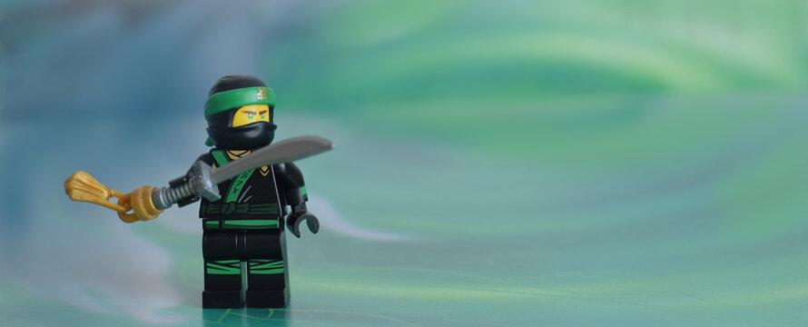 Editorial illustrative image of lego green ninja minifigure Lloyd on defocused background