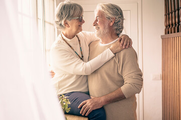 A moment of tenderness between two senior people who hug each other with love in front of the...