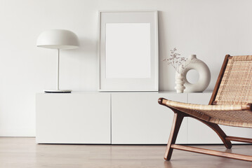 Blank picture frame mockup on white wall. White living room design. View of modern scandinavian style interior with chair. Home staging and minimalism concept