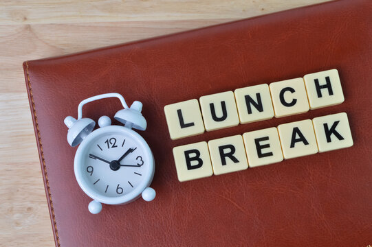 Top view of notebook, clock and alphabet letters with text LUNCH BREAK.