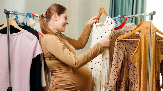 Pregnant smiling woman choosing and trying dresses hanging on clothes rack in her wardrobe at bedroom