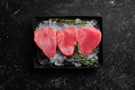 Raw tuna steak with spices on ice. On a dark background. Top view.