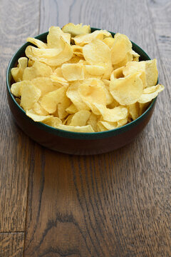 Large wood bowl of crispy Kettle potato chip snack on hardwood planks