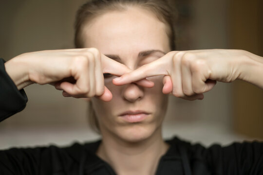 A young woman touches her nose because she loss of her sense of smell, does not feel the smell. Anosmia