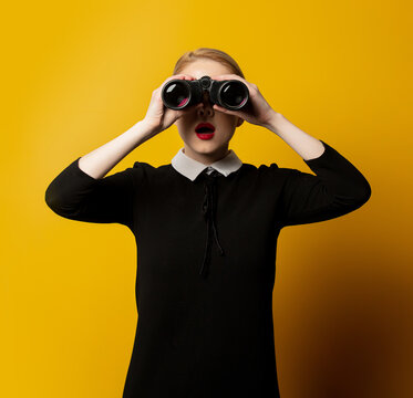 Style woman in black formal clothes with binocular on yellow background