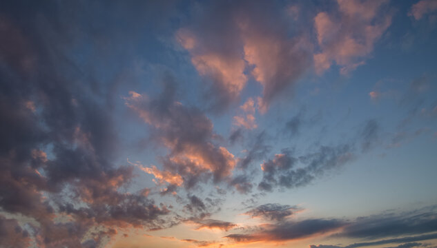 Natural color dramatic dawn or dusk sky with painterly yellow, pink and blue clouds with horizon, taken with wide angle 35 mm lens for sky replacement