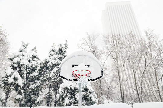 Front view of a street basketball hoop under the snow during the heavy Filomena storm in Madrid, Spain.