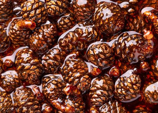 Small pine cones in sugar syrup. Pine cones background.