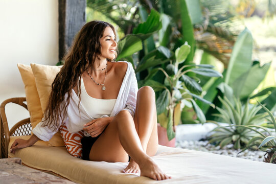 Home lifestyle woman relaxing enjoying luxury sofa on outdoor patio living room. Young female sitting on green garden terrace