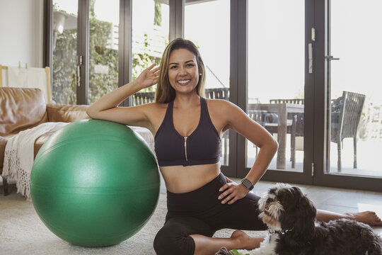 Portrait of beautiful Brazilian woman in sportswear with fitness ball and her pet dog, home exercise workout, online fitness class concept