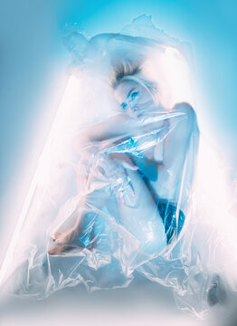 Abuse protection. Defocused art portrait. Mental recovery. Domestic violence. Distracted woman in fetal position covered transparent plastic film isolated on white blue neon lighting background.