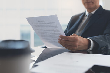 Signing contract, business agreement and deal concept. Closeup businessman reading before signing...