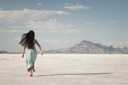 Gril in long blue dress running away on white salt flats, Bonneville, Utah, USA