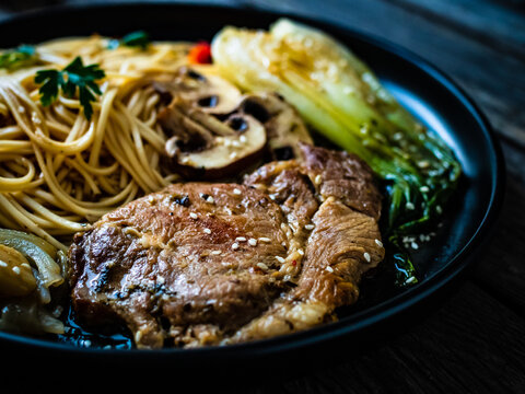 Fried pork steaks with mushrooms, noodles and steamed pak choi cabbage served on wooden table