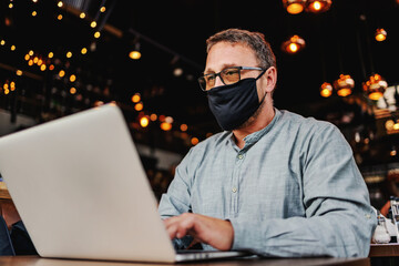 Middle aged serious freelancer with eyeglasses and protective mask on sitting in a cafe and using...