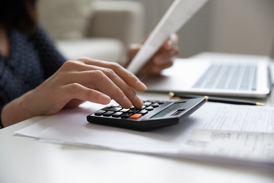 Close up young mixed race woman calculating domestic expenses involved in financial paperwork indoors, focused lady managing monthly banking payments summarizing utility bills and taxes at home.