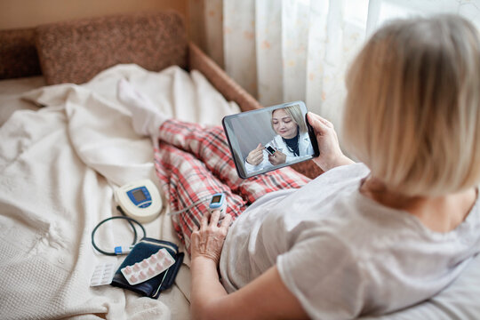 Old woman in bed looking at screen of laptop and consulting with a doctor online at home, telehealth services during lockdown, distant video call, modern tech healthcare application