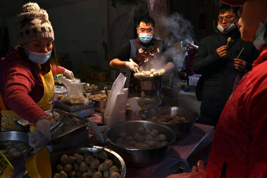 People wear protective masks while selling meatballs in a market in Taipei