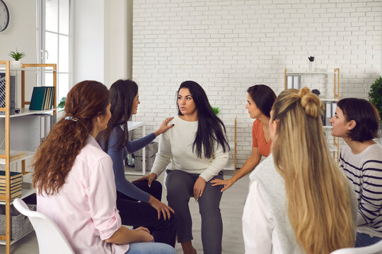 Women sharing their true stories in therapy session or support group meeting. Young friends talking, sharing news, discussing life situations, giving each other advice and helping cope with problems