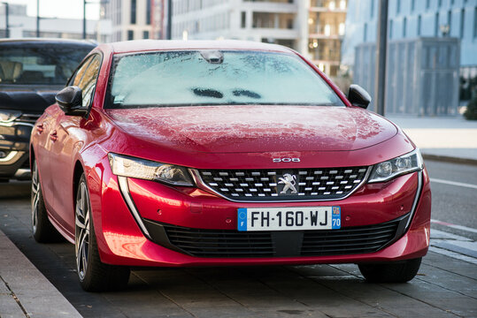 Mulhouse - France - 10 January 2021 - Front view of red Peugeot 508 covered by freeze parked in the street