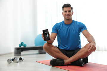 Man showing smartphone with fitness app indoors. Space for text