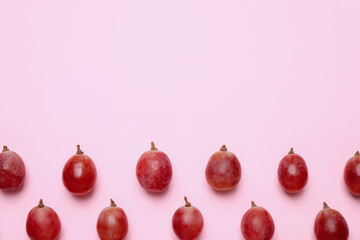 Flat lay composition with fresh ripe grapes on pink background. Space for text