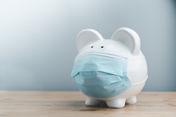 Piggy bank wearing surgical face mask. Global economy during coronavirus pandemic.  Financial...