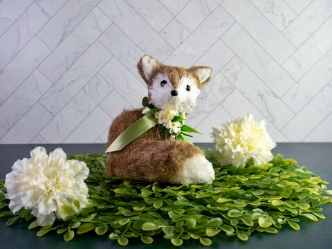 Spring fox animal adorned with yellow flowers and a green ribbon bow sitting on green leaves with white carnations and a herringbone tile behind it.