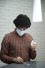 Fototapeta A handsome curly-haired man in a mask in a plaid shirt makes a rapid test for antibodies to coronavirus Covid 19 at home. He opened a rapid test kit, pricked his finger, and tested for Ig G and Ig M obraz
