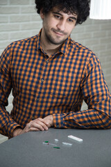 Fototapeta A handsome, solid curly-haired man in a plaid shirt makes a rapid test for antibodies to coronavirus covid 19 at home. He opened a rapid test kit, pricked his finger, and tested for Ig G and Ig M. obraz