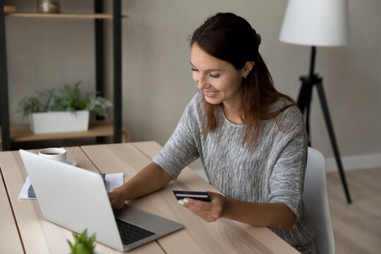 Smiling young Caucasian woman shopping online on laptop at home with credit card. Happy millennial female client or buyer make internet purchase or order on computer, use secure banking system app.