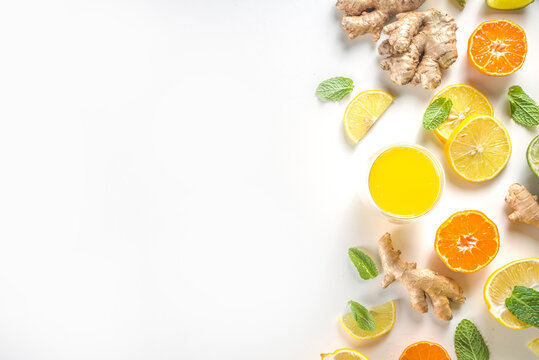 Immunity booster drink ingredients. Homemade ginger and citrus juice or cocktail, with fresh citrus fruit - orange, lemon, lime, with ginger root and mint leaves. White background top view copy space