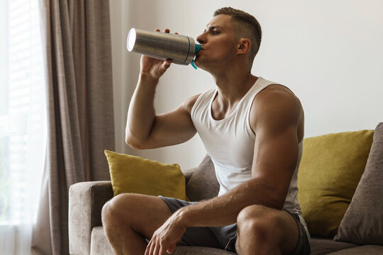 Man drinking protein shake after home workout