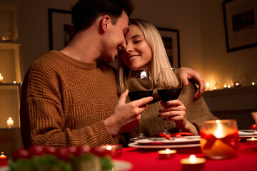 Fototapeta Happy young couple in love hugging holding glasses, drinking wine, celebrating Valentines day dining at home together, having romantic dinner date with candles sitting at table, embracing and bonding. obraz