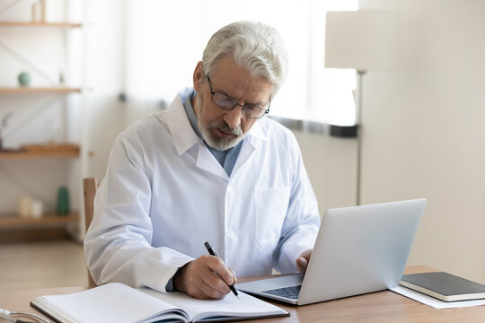 Focused middle aged male doctor in white uniform and eyeglasses leaving notes in paper journal, managing patient's checkup meetings or prescribing illnesses treatment, using computer at clinic office.