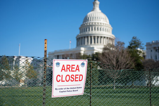 Area Closed sigh on Fence on blurred United States Capitol Building background.